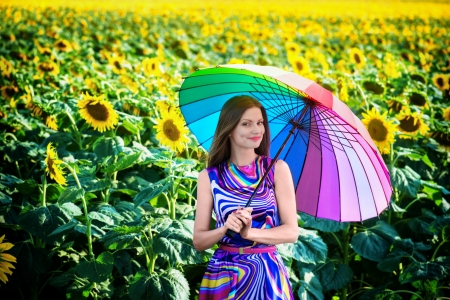 Portrait of a pretty smiling girl with colorful umbrella in the sunflower fields photo