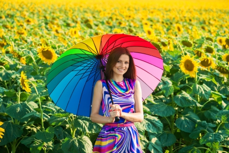 nice weather: Pretty smiling girl with colorful umbrella in the sunflower fields Stock Photo