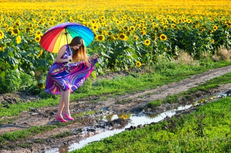 mud woman: Pretty girl with colorful umbrella trying to walk over mud puddle on the rural path