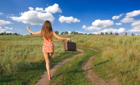 return trip: Happy girl walking in the countryside, view from back Stock Photo