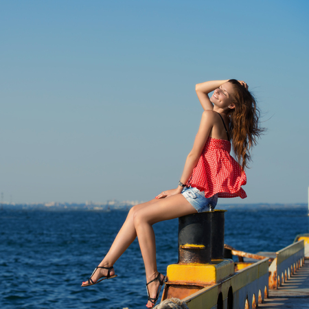 Pretty smiling girl sitting at the old berth in summer day photo