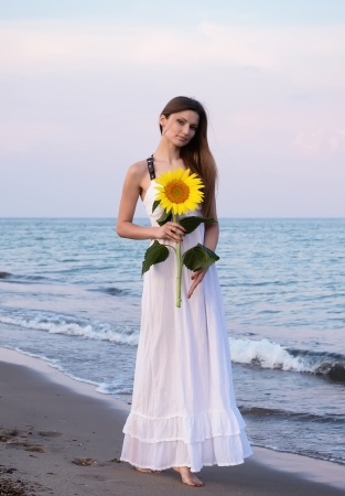 Girl in white dress with sunflower in her hands posing for photo at the beach photo