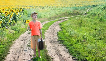 return trip: Boy with an old travelling bag standing on the provincial road