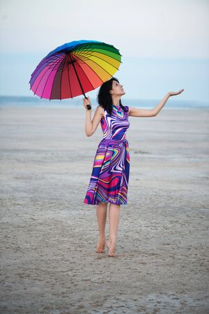 barefooted: Barefooted woman with colorful umbrella walking under the rain Stock Photo