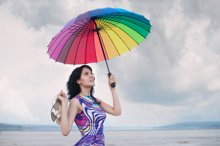 Pretty woman with colorful umbrella and with the white sandals in her hand photo