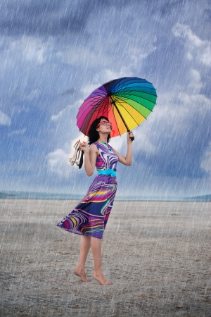 Barefooted woman with colorful umbrella under the rain photo