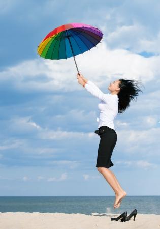 donna volante: Donna volare via dai suoi problemi con un ombrello colorato Archivio Fotografico
