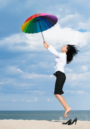at ease: Woman flying away from her problems with a colorful umbrella