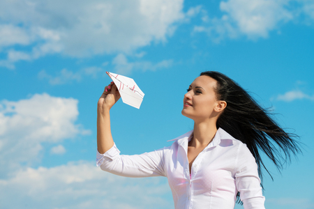 Young office lady with paper plane, outdoors portrait photo