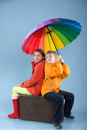 Girl and boy with a colorful umbrella sitting on an old traveling bag photo