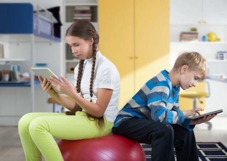 Girl and boy sitting on a big rubber ball and looking at Pad Tablet PC screens photo
