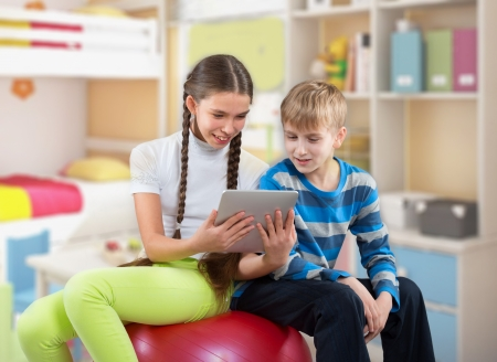 Girl and boy looking at a Pad Tablet PC screen and smiling photo