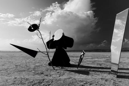 dunce cap: Strange figure in black cloak with the mirror face in desert  Artwork Stock Photo