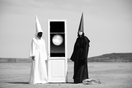 two visions: Two strange people in black cloak and white cloak and the door into another world  Artwork Stock Photo