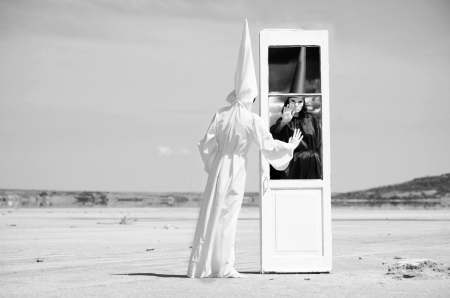 subconsciousness: Strange figures in black cloak and white cloak standing on either side of a door in the desert  Artwork