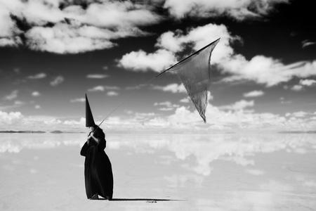 dunce cap: Strange figure in cloak with black banner walking the desert  Artwork
