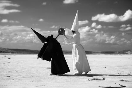 dunce cap: Strange figure in white cloak winding up another figure in black cloak in desert  Artwork