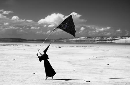dunce cap: Strange figure in cloak with the piece of night sky walking the desert  Artwork