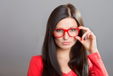 exacting: Pretty serious girl looking over glasses, studio shot on gray background Stock Photo
