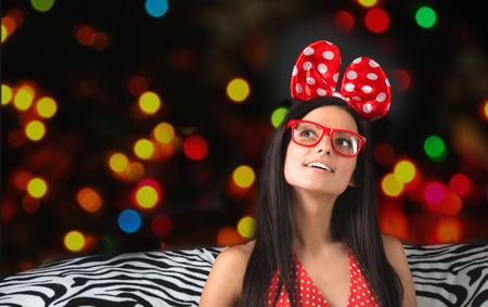 bow hair: Retrato de una chica divertida con un gran lazo del pelo y gafas mirando hacia arriba con las luces de colores sobre fondo oscuro