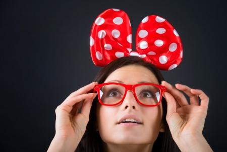 大きな髪弓とクローズ アップの肖像画、暗い背景を探しているメガネと驚く女の子