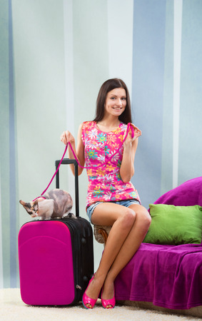 foretaste: Smiling pretty girl going on vacation with her cat