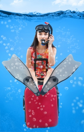 foretaste: Funny portrait of a girl with her travel luggage and snorkeling equipment sitting under the water Stock Photo