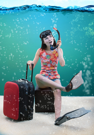 foretaste: Funny portrait of a girl with her travel luggage and snorkeling equipment sitting under the sea Stock Photo