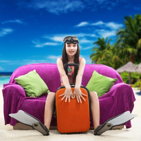 Funny portrait of a girl going on a vacation with her travel luggage and snorkeling equipment, against a tropical beach background
