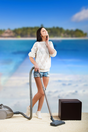 Pretty woman doing housework and dreaming of a beach vacation photo