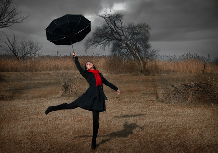 Woman with black umbrella turning inside out by the wind
