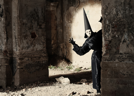 dunce cap: Stranger in white mask looking around the corner in an old ruined building