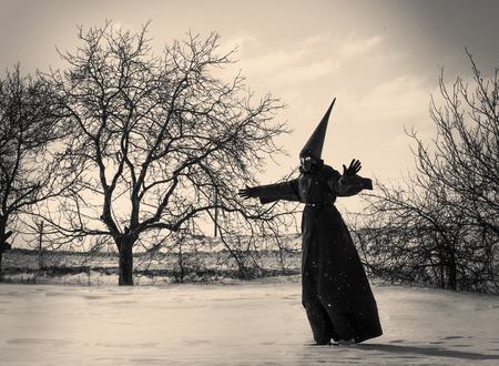 dunce cap: Black and white shot of a strange person in black cloak in winter day Stock Photo
