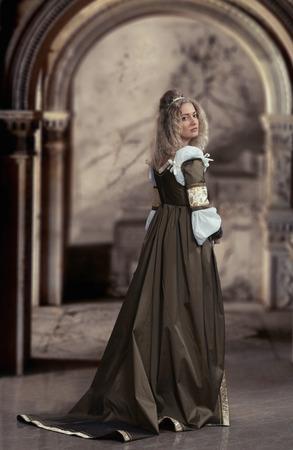 abito medievale: Donna in abito medievale, guardando indietro, antico sfondo interni