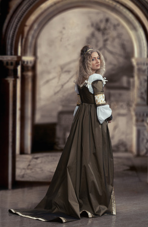 Woman in medieval dress looking back, antique interior background photo