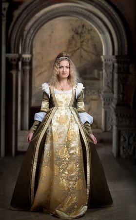middeleeuwse jurk: Vrouw in middeleeuwse kleding, antiek interieur achtergrond Stockfoto
