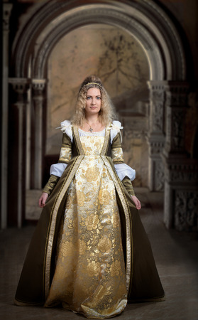 medieval dress: Woman in medieval dress, antique interior background