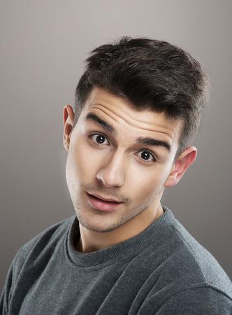 quizzical: Retrato de un joven hermoso que mira la c�mara con una expresi�n burlona en la cara, fondo gris