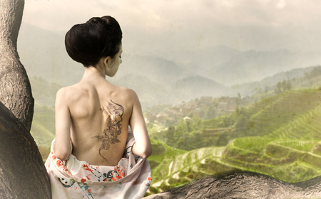 rural landscapes: Asian style portrait of young woman with snake tattoo on her back sitting on the tree branch Stock Photo