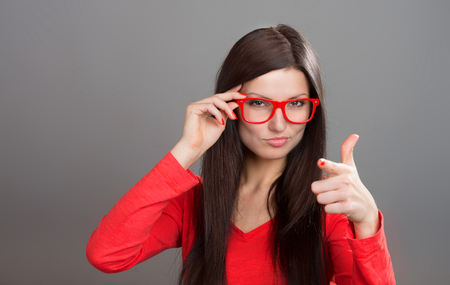 exacting: Skeptical woman in red-framed glasses pointing at camera, studio shot, gray background