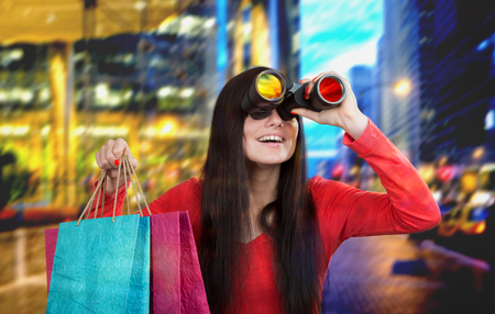 Smiling girl looking through the binoculars and looking for discount, city lights background photo