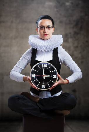 ruff: Business lady in ruff collar with a clock looking at camera