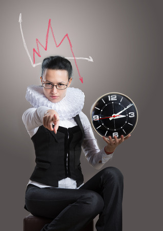 Business lady in ruff collar with a clock pointing at the camera photo