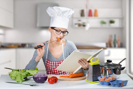 Pretty woman cooking with cookbook