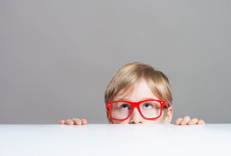 Serious boy in red-framed eyeglasses looking up from behind the table photo