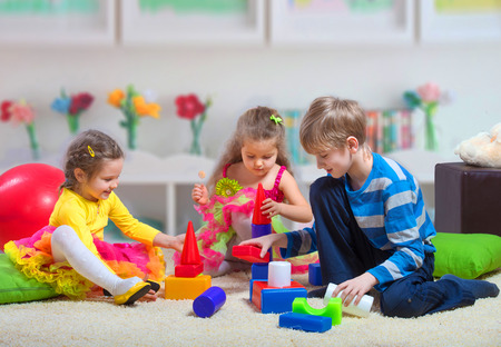 preteen boys: Preteen boy playing with two younger girls Stock Photo