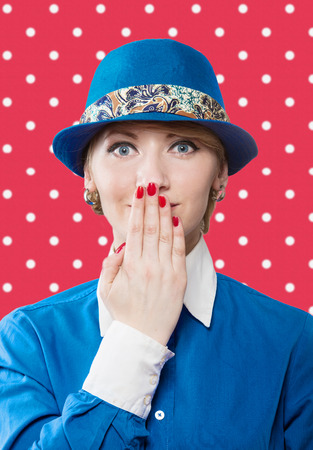 Portrait of a woman in a blue hat hiding a smile, red polka dot background