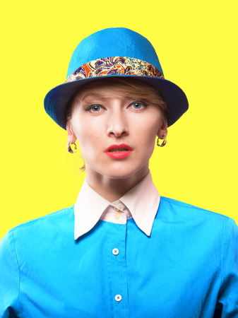 exacting: Portrait of a serious woman in a hat looking at camera, studio shot on yellow background