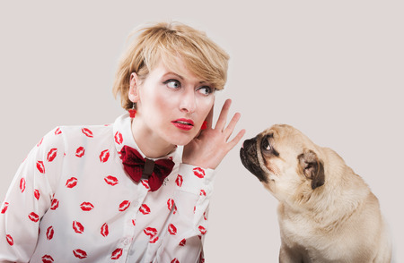 Vintage style woman listening to her dog Stock Photo