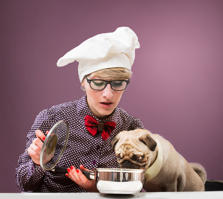 Woman in chef s hat and her dog tasting food, purple background photo